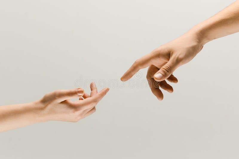 Duas mãos masculinas que tentam tocar isolado no fundo cinzento do estúdio fotografia de stock royalty free