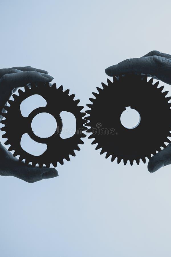Duas mãos que mantêm o ferro, roda denteada do metal unido foto de stock royalty free