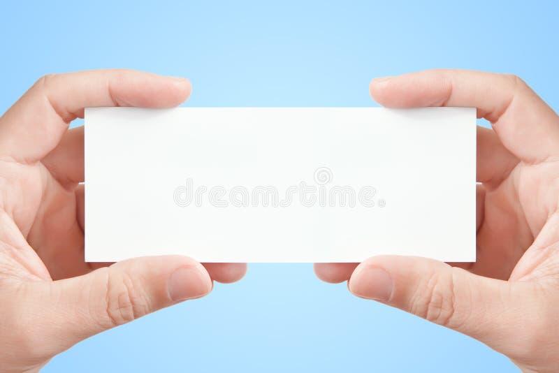 Duas mãos que prendem o cartão de papel em branco foto de stock royalty free