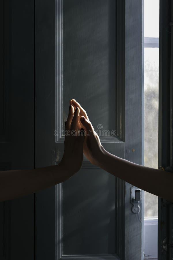 Duas mãos que tocam-se em na frente de uma janela azul iluminada pelo ` s do sol irradiam foto de stock