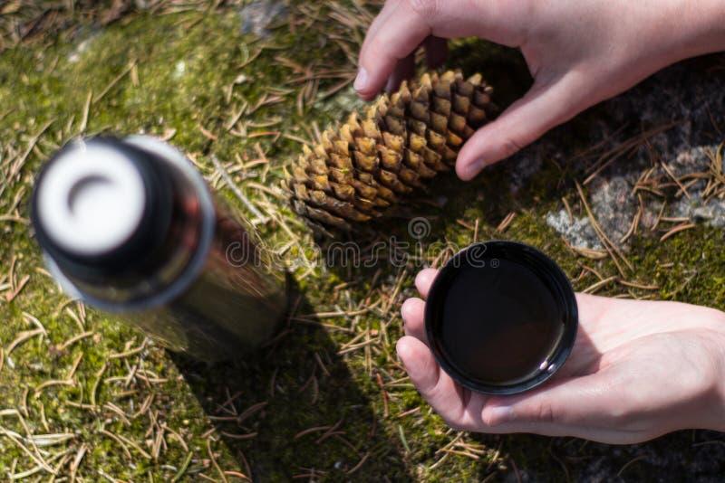 Duas m?os guardam o copo do ch? ou do coffe quente na rocha musgoso fotos de stock royalty free