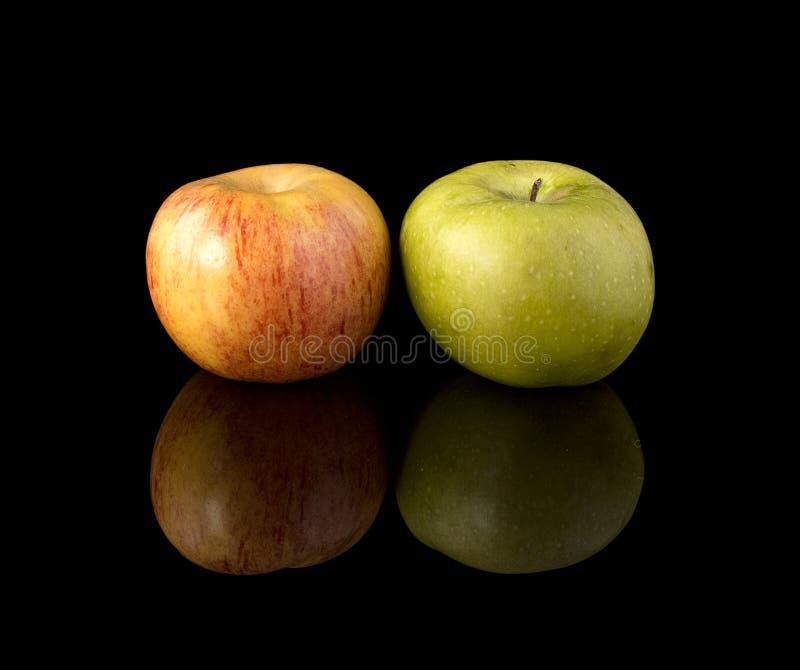 Duas maçãs em uma superfície preta do espelho foto de stock royalty free