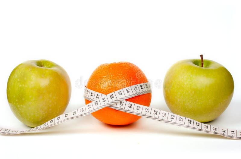 Duas maçãs verdes e uma laranja com fita. fotografia de stock royalty free