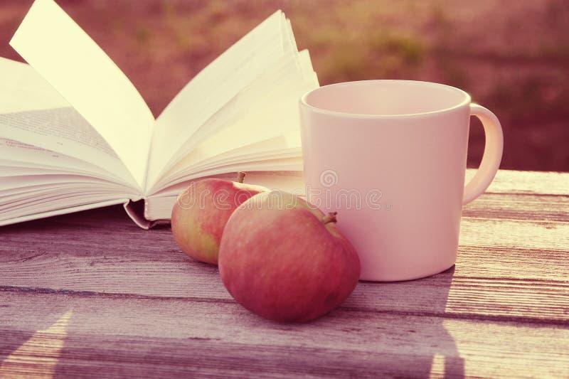 Duas maçãs vermelhas, caneca cor-de-rosa e livro aberto no banco de madeira nos raios de luz solar foto de stock