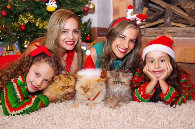 Duas mamãs bonitas com suas meninas, vestindo um Natal vesti-se-rem, a menina encaracolado com um laço vermelho em seu cabelo qua foto de stock royalty free