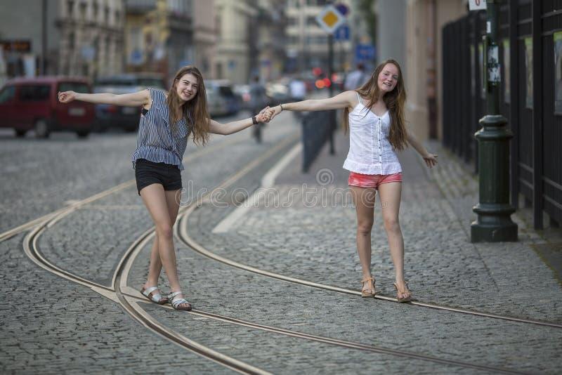 Duas melhores amigas novas andam ao longo das trilhas do bonde na cidade velha imagem de stock royalty free
