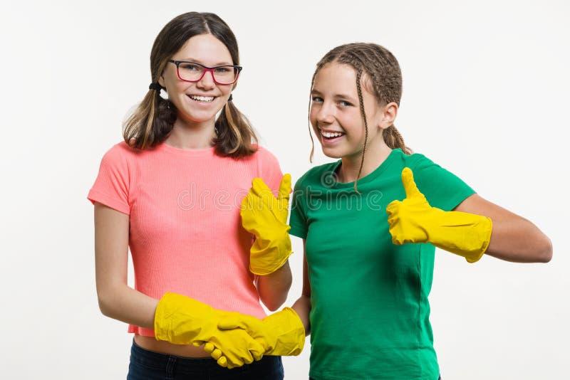 Duas meninas adolescentes com as luvas amarelas da limpeza que agitam as mãos mantêm seu dedo acima no backgrounde branco imagem de stock