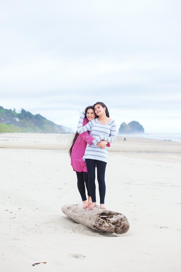 Duas meninas adolescentes que abraçam e que riem da praia fotografia de stock royalty free