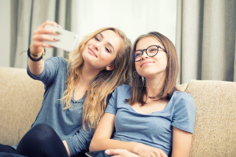 Duas meninas adolescentes sorriem e tomam um selfie junto fotos de stock royalty free