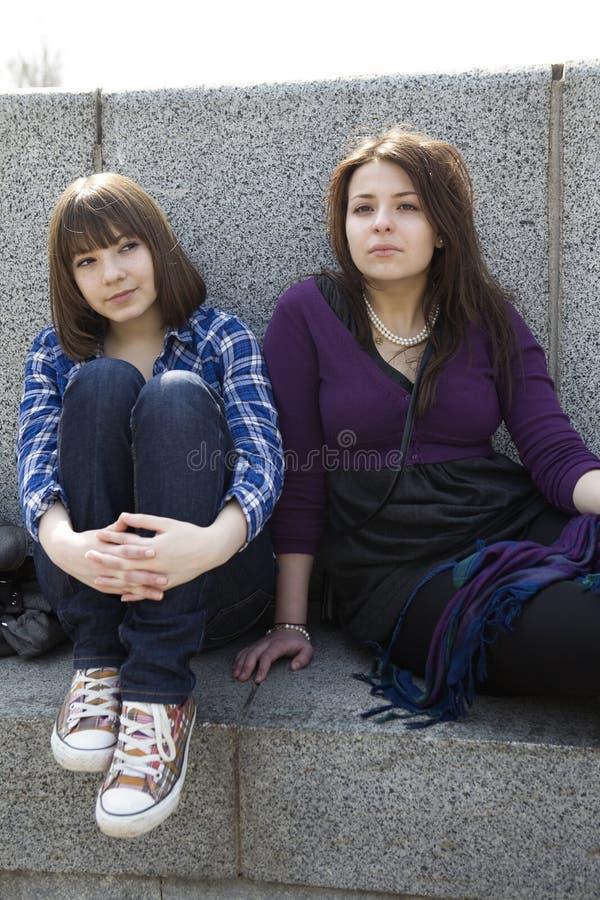 Duas meninas adolescentes urbanas que sentam-se em escadas fotos de stock royalty free