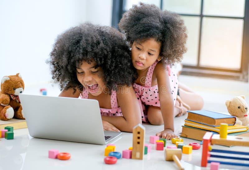 Duas meninas africanas novas jogam com o laptop entre brinquedos, boneca e livro na frente da janela de vidro imagem de stock
