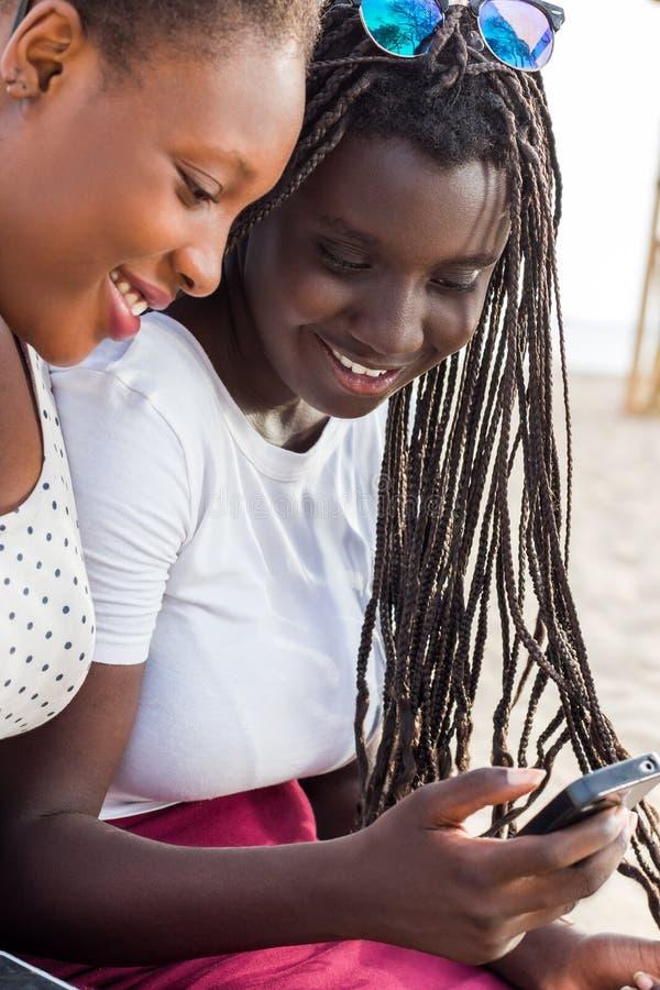 Duas meninas africanas que olham junto no telefone esperto imagem de stock royalty free