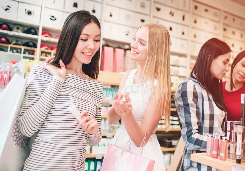 Duas meninas agradáveis na parte dianteira estão estando e estão sorrindo A menina asiática está olhando os cosméticos que a meni imagens de stock royalty free