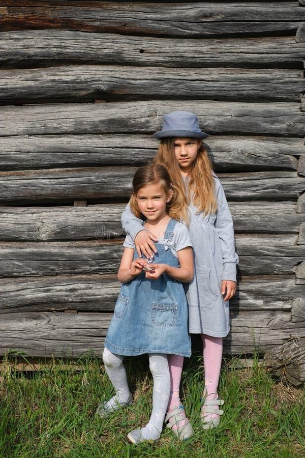 Duas meninas alegres das irmãs na roupa ocasional azul que levanta por uma parede de madeira Estilo de vida ativo Forma da juvent foto de stock royalty free