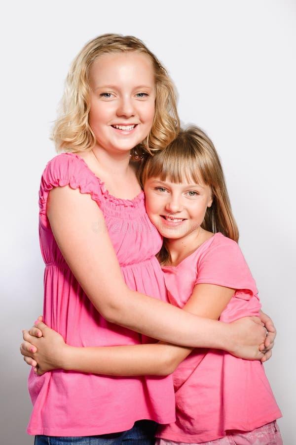 Duas meninas alegres do preteen que abraçam como melhores amigos imagem de stock royalty free