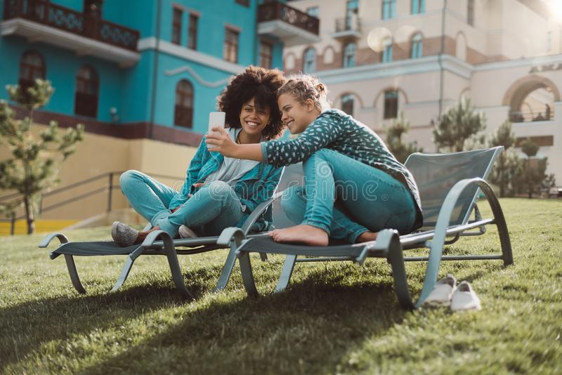 Duas meninas alegres no prado da mola com telefone celular fotografia de stock royalty free
