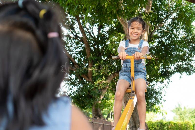 Duas meninas asiáticas bonitos da criança que jogam a balancê junto no campo de jogos fotografia de stock