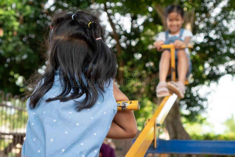 Duas meninas asiáticas bonitos da criança que jogam a balancê junto no campo de jogos fotografia de stock royalty free