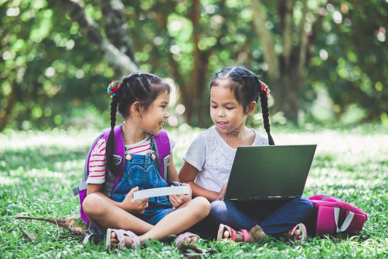 Duas meninas asiáticas bonitos da criança que usam o portátil no parque junto fotos de stock royalty free