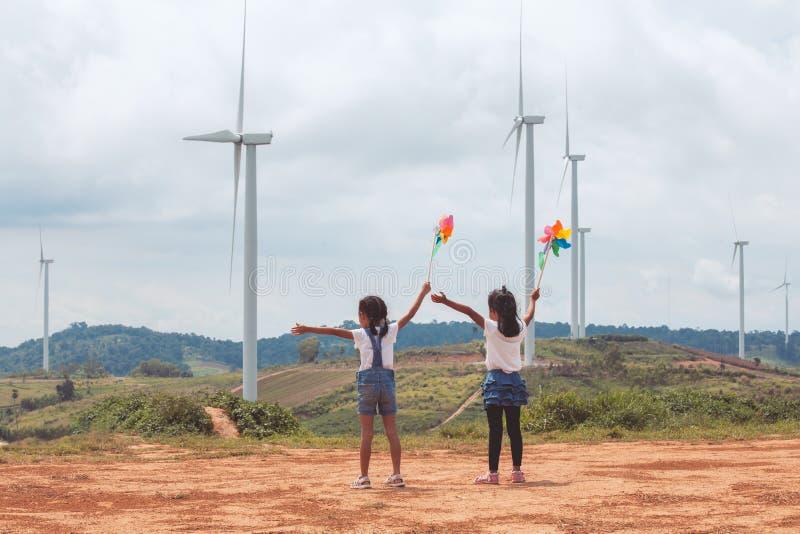 Duas meninas asiáticas da criança que jogam com brinquedo da turbina eólica e que olham o campo da turbina eólica junto fotos de stock