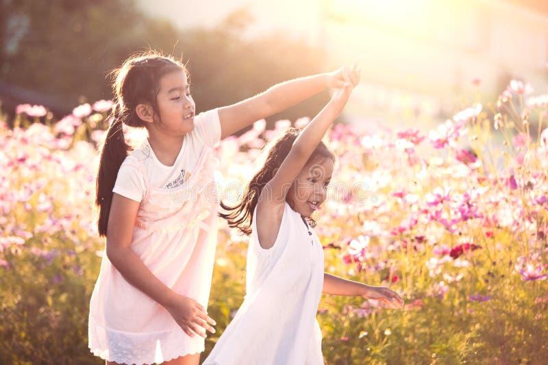 Duas meninas asiáticas da criança que têm o divertimento a jogar junto e dançar imagens de stock royalty free