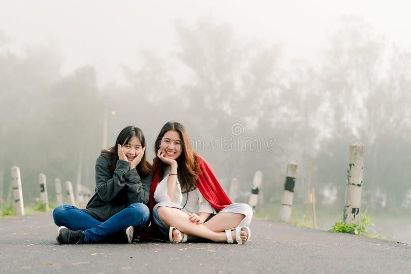 Duas meninas asiáticas fecham muito os amigos que vestem uma camiseta nas atrações turísticas ao longo da estrada ao lado do rese foto de stock