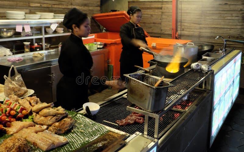 Duas meninas asiáticas preparam o alimento, café do alimento da rua imagens de stock