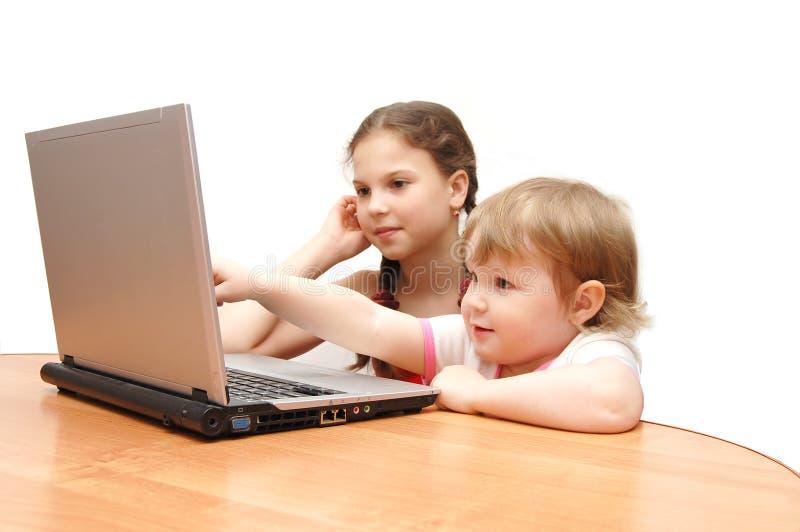 Duas meninas atrás do portátil foto de stock