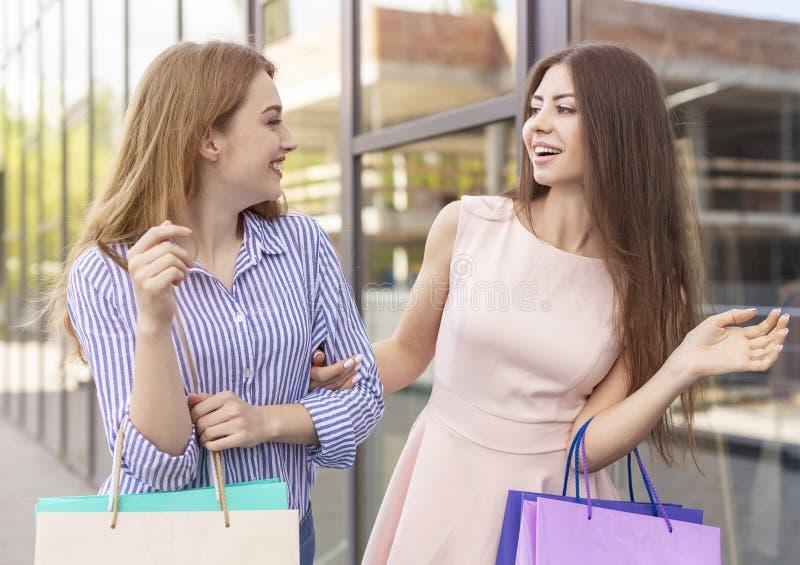 Duas meninas atrativas que falam entre si, sacos de papel levando foto de stock