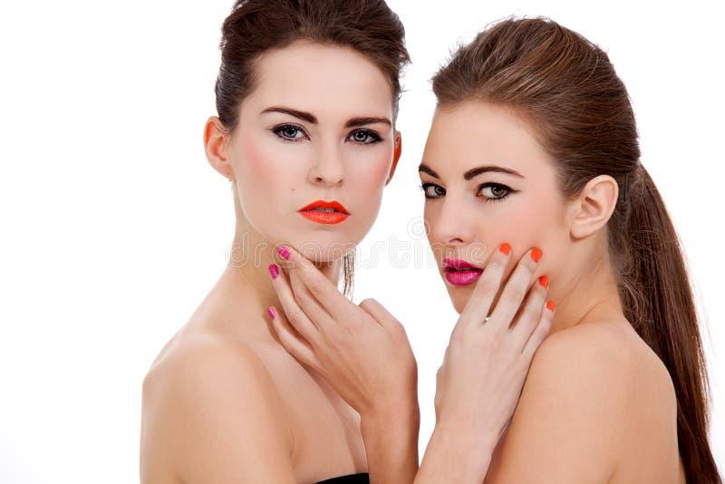 Duas meninas bonitas com composição do colorfull isoladas imagens de stock