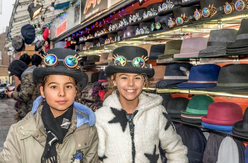 Duas meninas bonitas com os chapéus em Londres fotografia de stock