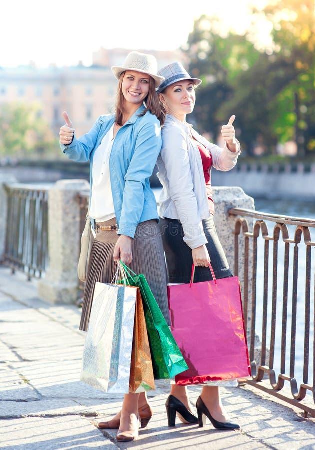 Duas meninas bonitas com os sacos de compras que mostram os polegares acima fotografia de stock royalty free