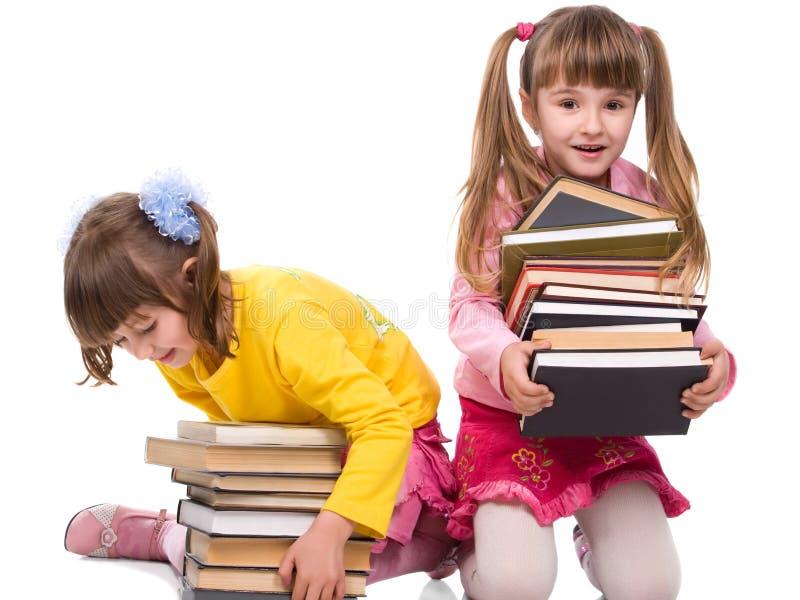Duas meninas bonitas com a pilha de livros fotografia de stock royalty free