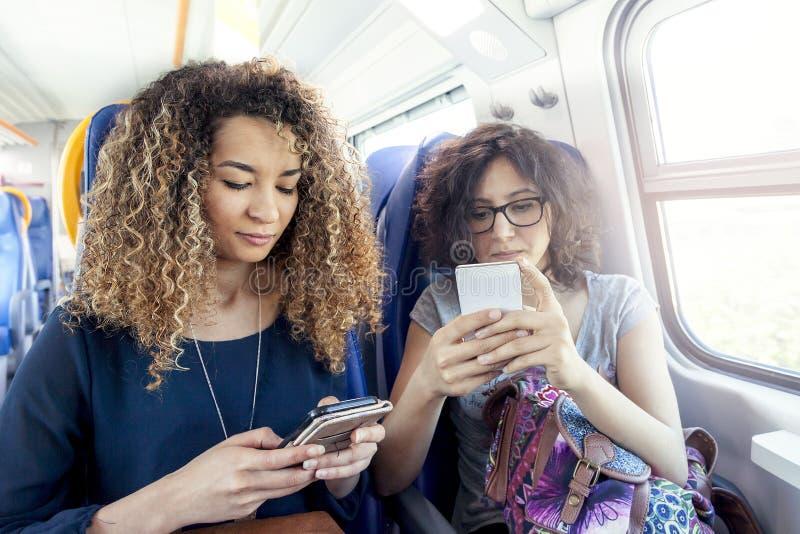 Duas meninas bonitas de sorriso que usam um smartphone foto de stock
