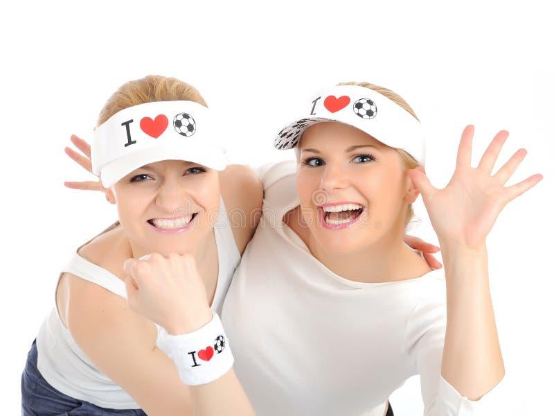 Duas meninas bonitas do fan de futebol em chapéus engraçados foto de stock royalty free