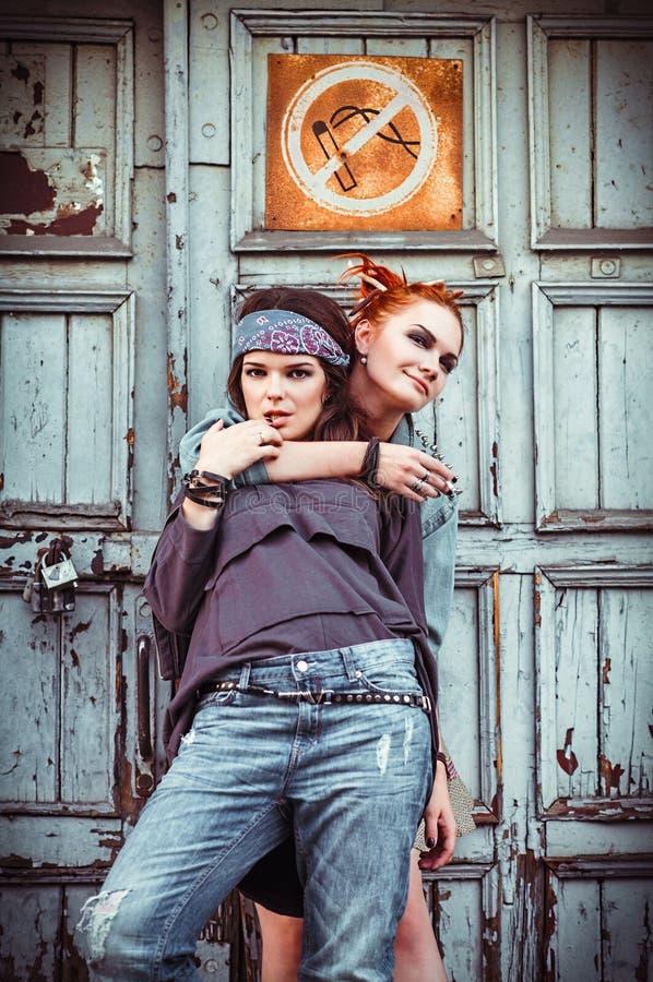 Duas meninas bonitas do grunge que estão em uma parede imagens de stock