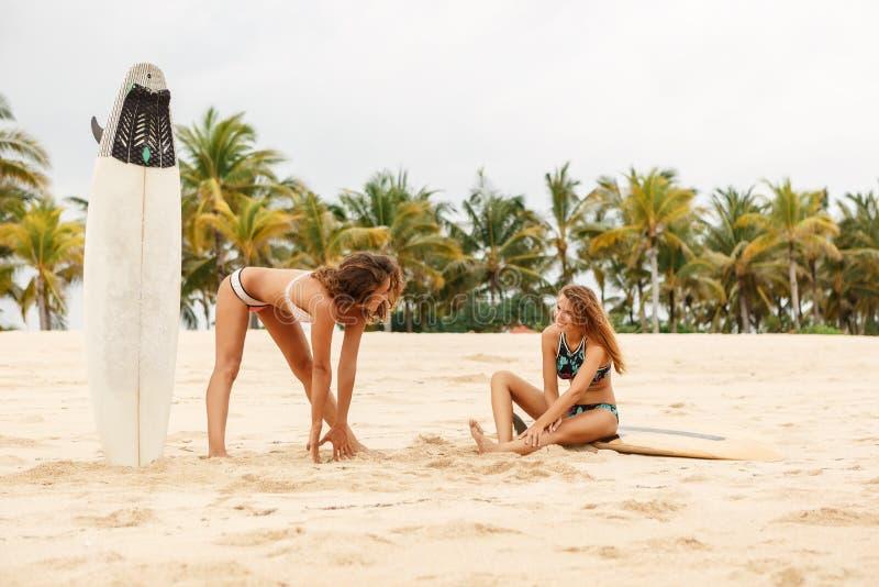 Duas meninas bonitas do surfista fazem um aquecimento na praia foto de stock
