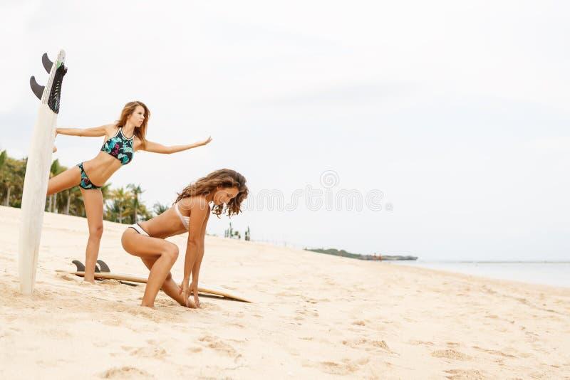 Duas meninas bonitas do surfista fazem um aquecimento na praia imagens de stock royalty free