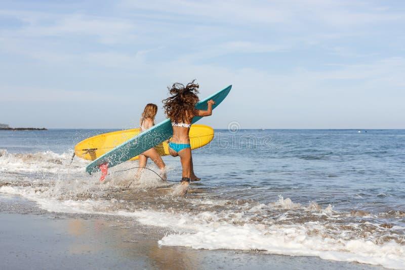 Duas meninas bonitas do surfista na praia entram na água foto de stock