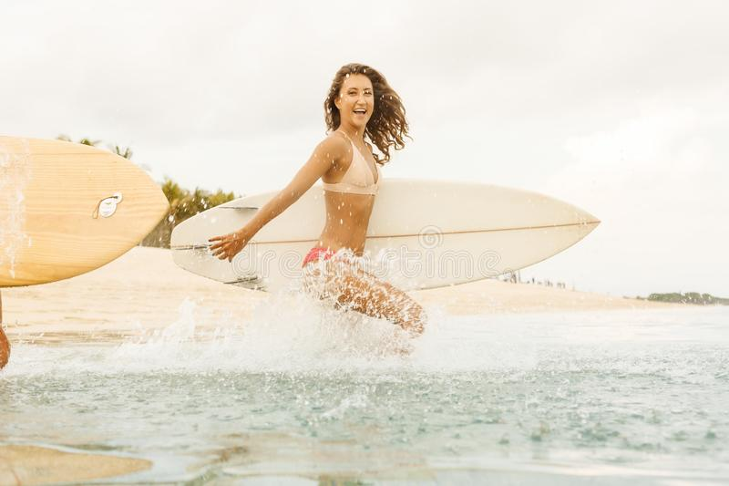 Duas meninas bonitas do surfista na praia entram na água fotografia de stock royalty free