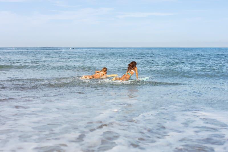 Duas meninas bonitas do surfista na praia entram na água imagens de stock