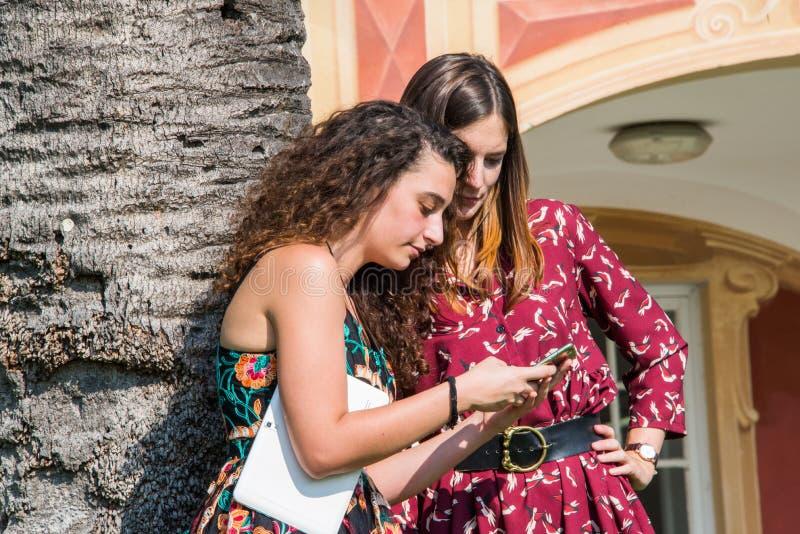 Duas meninas bonitas estão bisbilhotando sobre um perfil do facebook fotos de stock