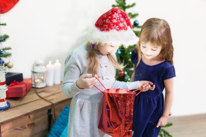 Duas meninas bonitas felizes olham no saco do feriado do Natal que incandesce do interior fotografia de stock royalty free