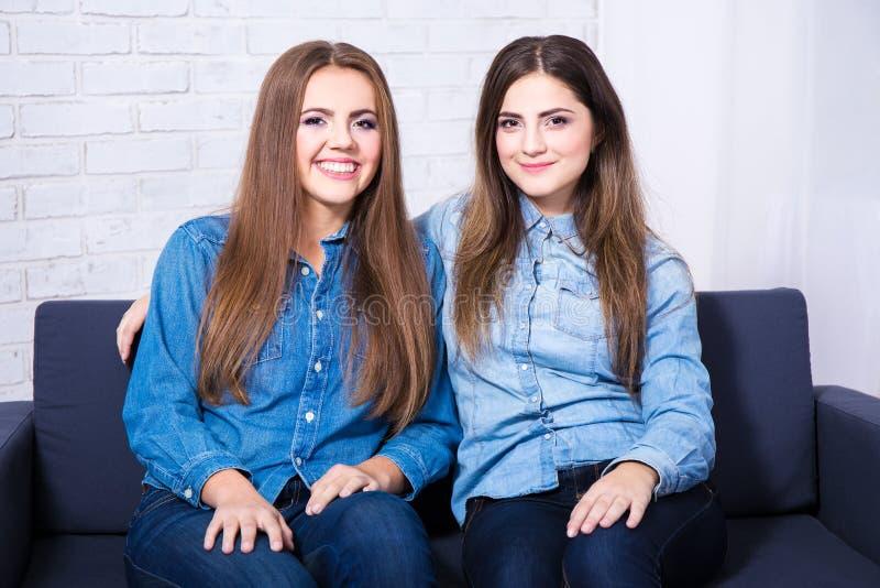 Duas meninas bonitas felizes que sentam-se no sofá na sala de visitas fotos de stock