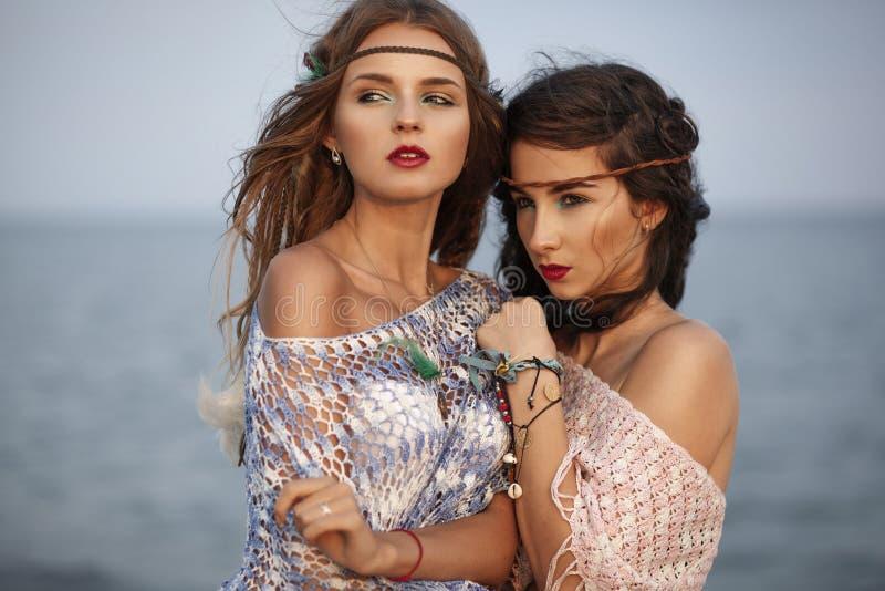 Duas meninas bonitas no estilo do boho da forma no mar imagens de stock