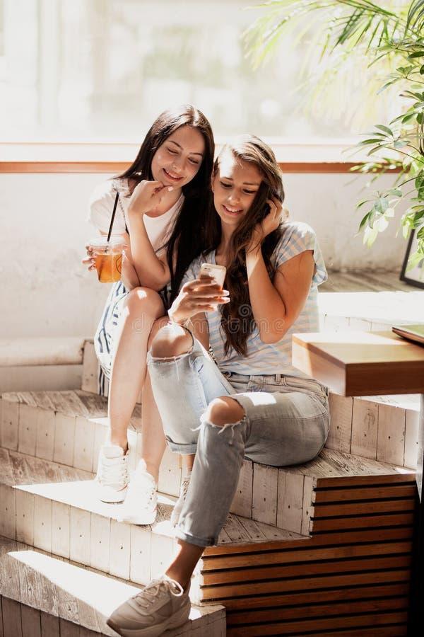 Duas meninas bonitas novas com cabelo escuro longo, equipamento ocasional vestindo, sentam-se nas escadas e olham-se o telefone e imagens de stock royalty free