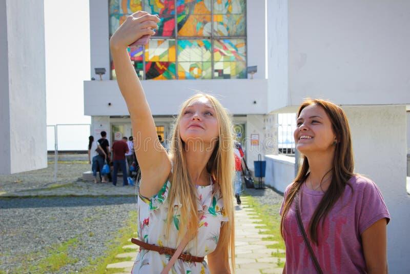 Duas meninas bonitas novas estão fazendo o selfie foto de stock