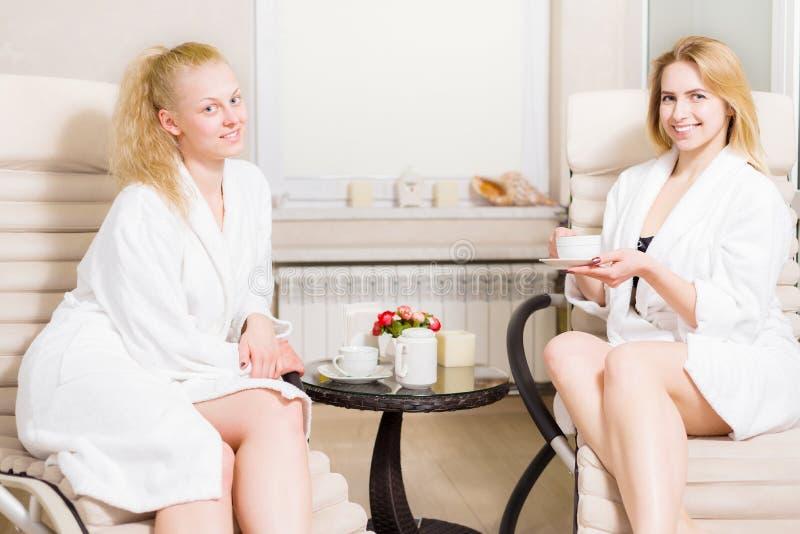 Duas meninas bonitas novas no salão de beleza dos termas mulheres bonitas nos louros brancos dos revestimentos para relaxar e beb fotografia de stock royalty free