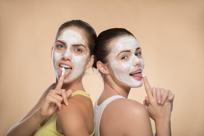 Duas meninas bonitas que aplicam a máscara de creme facial e imagem de stock