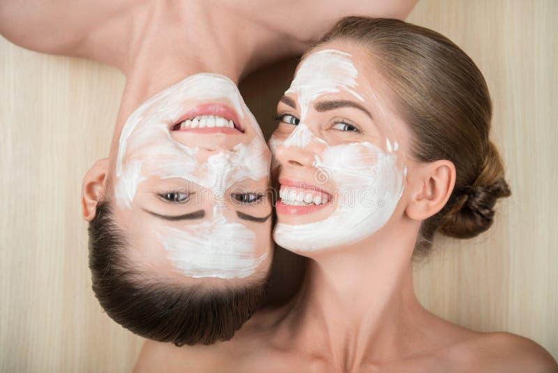 Duas meninas bonitas que aplicam a máscara de creme facial e imagem de stock royalty free